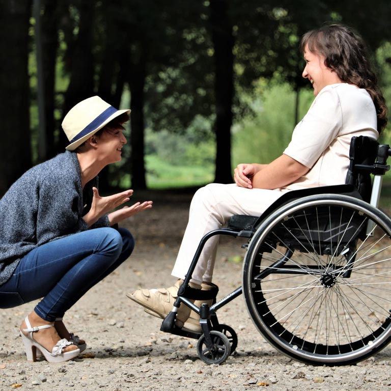 A squatting and smiling woman in front of a woman in a wheelchair, on a forest path
