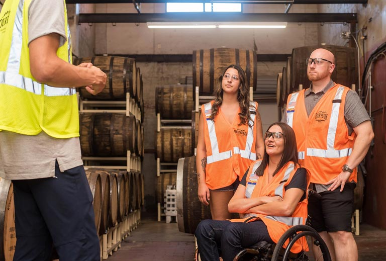 Two women, one in a wheelchair, and a man visiting a warehouse