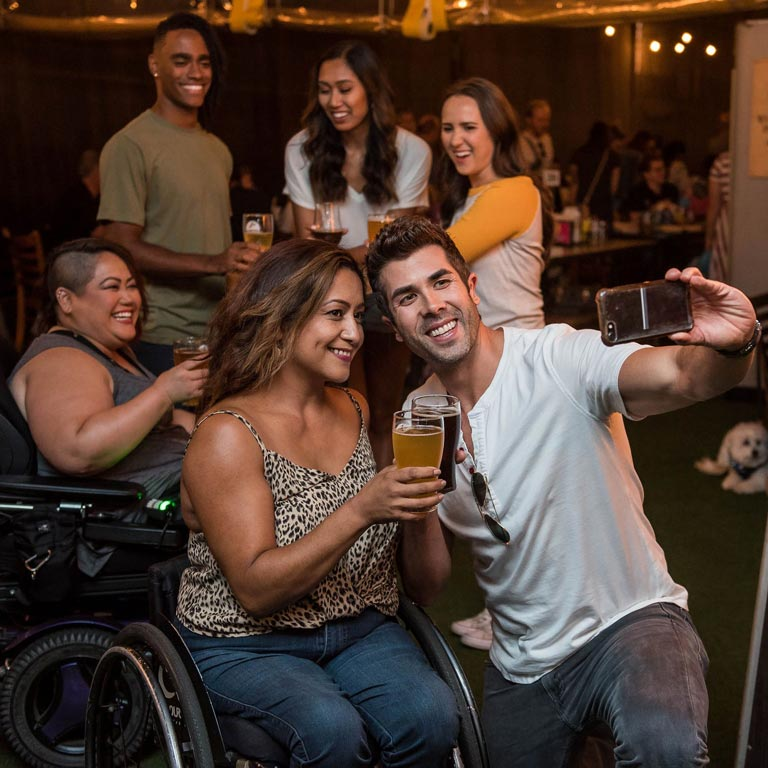 Four women (two are in a wheelchair) and two men taking a selfie dring a party.